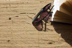 Sunglasses and book on sand Stock Photos