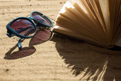 Sunglasses and book on sand Royalty Free Stock Images