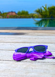 Sunglasses and bow tie near the pool Stock Photos