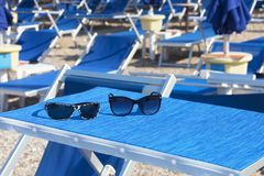 Sunglasses on a bright blue chaise longue royalty free stock photography