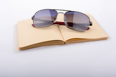 Sunglasses and a brown notebook Stock Photo