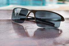 Sunglasses on brown wood table near swimming pool Stock Photos