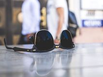 Sunglasses on a cafe table. A pair of sunglasses on a cafe table, with some people walking by stock image