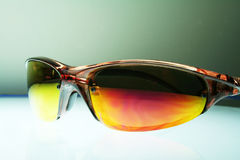 Sunglasses can be used to hide the eyes. A pair of sunglasses on illuminated glass Royalty Free Stock Images