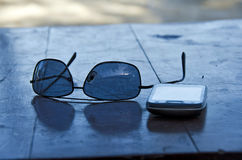 Sunglasses and cell phone. On the table Royalty Free Stock Photos