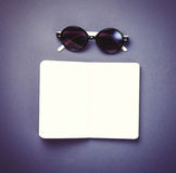 Sunglasses and classic notebook on violet background. Royalty Free Stock Photos
