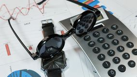 Sunglasses, clock and calculator lie on the background of the diagrams. Ideas and concepts of business. Stock Images