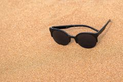 Sunglasses closeup on the sandy coast. One sunglasses of black color are located separately a closeup on the sandy coast and a blank space Royalty Free Stock Image