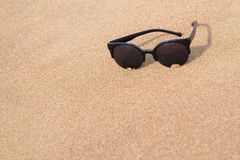 Sunglasses closeup on the sandy coast Royalty Free Stock Photos