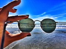 Sunglasses and sea. Woman's hand holding a pair of sunglasses next to coastline on sunny day Royalty Free Stock Images
