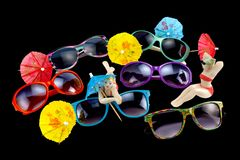 Multicolored sunglasses, umbrellas and porcelain figurines on a royalty free stock photo