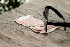 Sunglasses with coins and bank notes on the background of wood. Royalty Free Stock Images