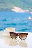 Sunglasses and cup against sea Stock Images