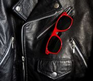 Sunglasses with dark spectacle lens and red frame in a pocket of a studded jacket. Sunglasses with dark spectacle lens and red frame in a pocket of a black Stock Photography