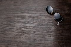 Sunglasses on a dark wooden table stock image