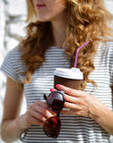 Sunglasses and Disposable Coffee Cup in the woman hands Stock Photo