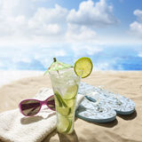 Sunglasses drink in sand on beach. At sea holiday concept Stock Photo
