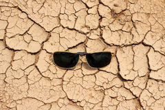 sunglasses on dry crack earth texture Royalty Free Stock Photo