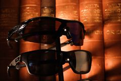 Sunglasses at dusk in a warm mood in an old library royalty free stock photo