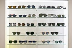 Sunglasses and Fashion Eyewear in a shop window optician. Exhibitor of glasses consisting of shelves of fashionable glasses shown on a wall at the optical shop Stock Photography