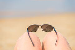 Sunglasses on female kneeling Stock Images