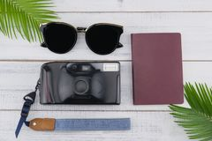 Sunglasses, film camera and passport with fern leaves. On white wood background Royalty Free Stock Photos