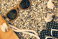 Sunglasses, flip flop sandals and beach bag on the beach Royalty Free Stock Images