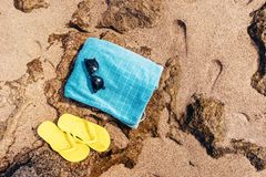 Sunglasses, flip flops, blue towel ready for sunbathing on a sunny afternoon. at beach. Sunglasses, yellow flip flops, blue towel ready for sunbathing on a sunny royalty free stock images