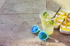 Sunglasses, flipflops and mojito glass. On stone background royalty free stock photography