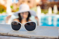 Sunglasses in the foreground and the background is blurred woman in the pool Royalty Free Stock Images