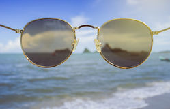 Sunglasses front of the camera,looked like wearing a sunglasses,blurred sea in background,selective focusat center of sunglasses Stock Photos