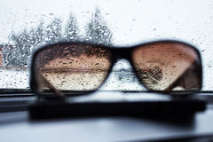 Sunglasses in front of a wet windshield. Wet windshield behind sunglasses laying on a dashboard Stock Image