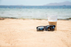 Sunglasses and glass on the sand. Near the sea Royalty Free Stock Photo