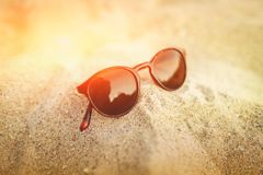 Sunglasses on the golden sand with reflections in the glass. Seascape ocean and beautiful beach paradise. Summer vacation concept. Close up Stock Photos