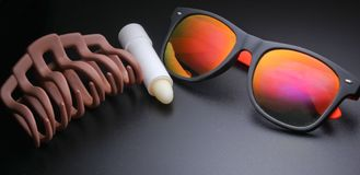 Sunglasses, hair clip, hygienic lipstick stock images