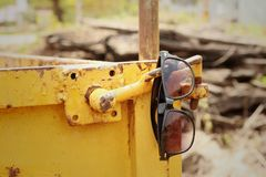 Sunglasses hanging on yellow steel at the park. Stock Photos