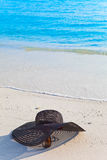 Sunglasses and  hat lay on sand at edge of sea Stock Images