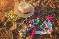 Sunglasses with hat on sand. Colorful swimsuit and flip flops. Style of summer. Get away from the bustle Royalty Free Stock Photos