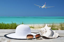 Sunglasses, hat and shell against ocean Stock Photos