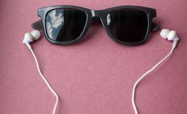 Sunglasses and headphones on pastel pink background stock photos