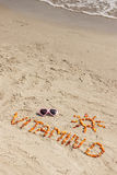 Sunglasses, inscription vitamin D and shape of sun on sand at beach, summer time and healthy lifestyle. Sunglasses, inscription vitamin D and shape of sun made Royalty Free Stock Photo
