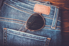 Sunglasses on jean pants retro vintage style Stock Images