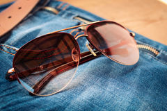 Sunglasses on jeans background. Toned image Royalty Free Stock Photography