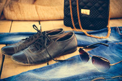 Sunglasses, jeans, handbag and old shoes. Toned image. Royalty Free Stock Photo