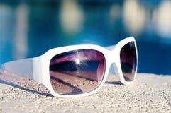 sunglasses laying beside swimming pool Stock Image