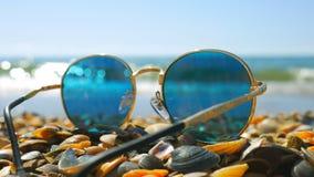 Sunglasses left on the seashells beach, focus on the seashells. The girl is running on the beach stock footage