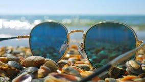 Sunglasses left on the seashells beach, focus on the seashells. Sunglasses left on the seashells beach, focus on the seashells stock footage