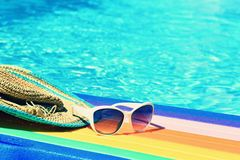 Sunglasses, lilo and hat on the water in hot sunny day. Summer background for traveling and vacation. Holiday idyllic. Royalty Free Stock Photography