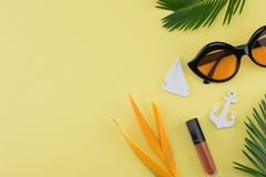 Sunglasses and lip gloss decorate with tiny sailboat, anchor. Bird of paradise flower and fern leaves on yellow background with copy space stock images
