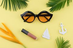 Sunglasses and lip gloss. Decorate with tiny sailboat, anchor, bird of paradise flower and fern leaves on yellow background Stock Photo